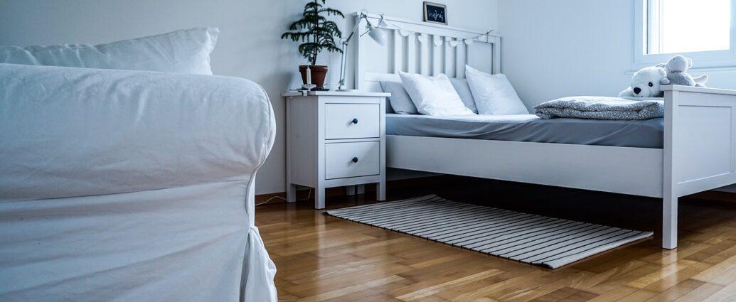 Biała sypialnia z drewnianą podłogą