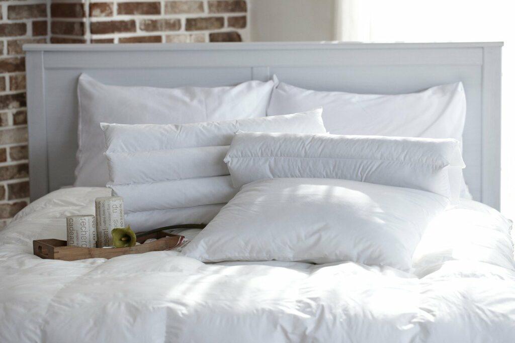 Białe dodatki do sypialni - białe poduszki oraz poszwa na kołdrę na łóżku z białym zagłówkiem