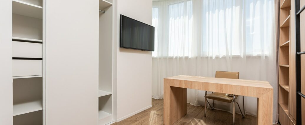 Biurko z naturalnego drewna w nowoczesnym pokoju z białymi meblami