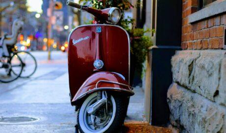 Czerwony skuter zaparkowany na uliczce w mieście