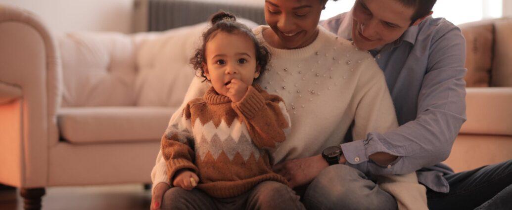 Rodzice z małym dzieckiem siedzącym na kolanach
