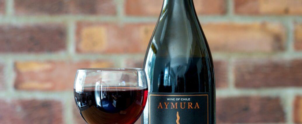 Kieliszek czerwonego wina i odkorkowana butelka - jak długo można trzymać otwarte wino