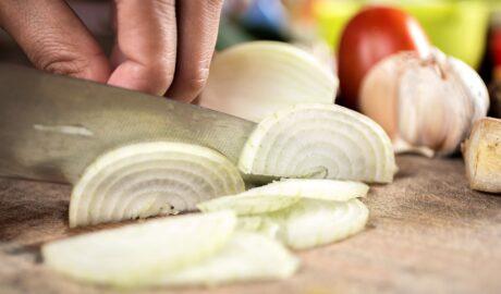 Kucharz kroi cebulę w półkrążki nożem szefa