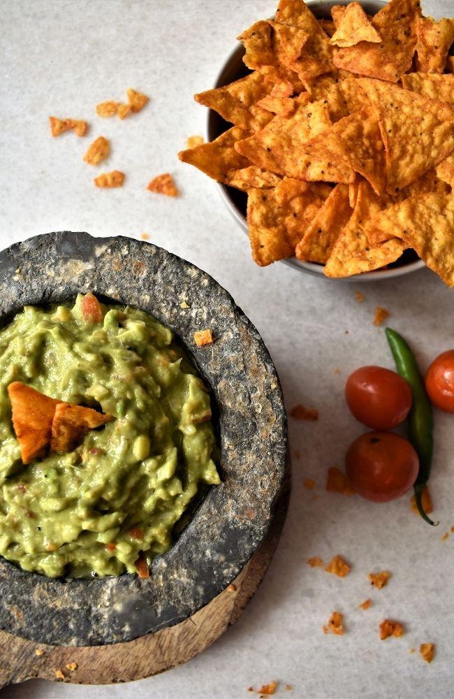 Guacamole w kamiennym naczyniu z nachosami i pomidorkami