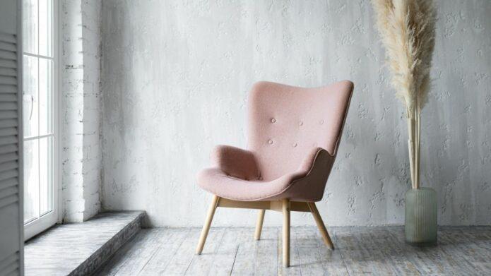 Krzesło w kolorze brudnego różu przy oknie na tle szarej ściany i dekoracji z suszonych traw