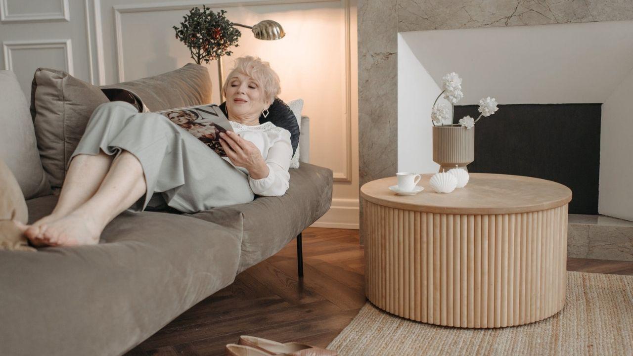 Starsza kobieta leży na sofie i czyta gazetę